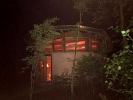 The Strawbale Studio lit up at night, photo by Sarah baker